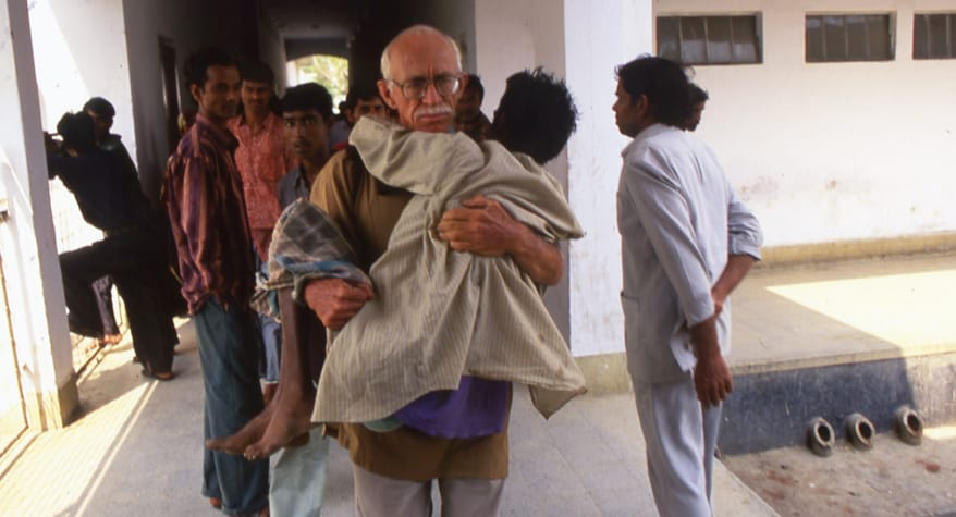 Father Bob McCahill, M.M. carrying a patient to the hospital (Bangladesh)
