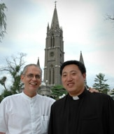 Fr. Brian Barrrons in front of the Jilin cathedral with Fr. Jin
