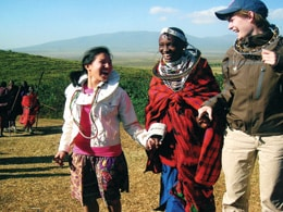 Maasai woman welcomes U.S. students Rachael Wolff (l.) and Caitlin Rooke to her village.
