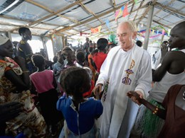 Maryknoll Father Mike Bassano greets people during the sign of peace at Mass April 9 in a makeshift chapel inside a U.N. base in Malakal, South Sudan. (CNS photo/Paul Jeffrey)