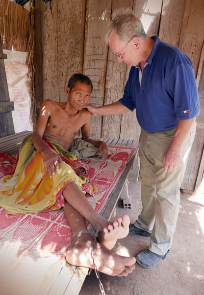 Father Kevin Conroy comforts a man suffering from mental illness (Cambodia)