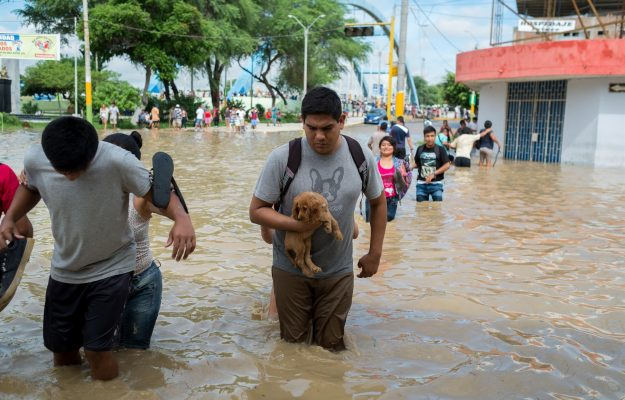People cross a street flooded by the Piura River March 27 in Peru. Catholics participating in the Peoples Climate Movement march April 29 in the nation's capital will be able to pray at a Mass and visit their representatives on Capitol Hill to discuss the issue of climate change. (CNS photo/Edwin Zapata Alvarado, EPA) See CLIMATE-MARCH-PRAYER April 5, 2017.